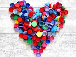 Photo de bouchons d'amour de toutes les couleurs réunis en forme d'un grand coeur